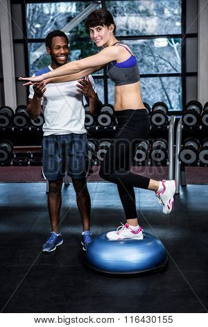 Fit woman with trainer exercising with bosu at gym