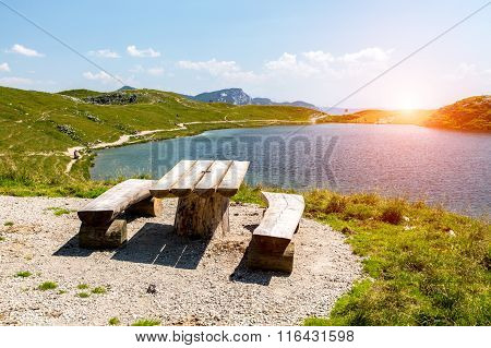 Sunset Above The Bench At The Shore Of The Lake