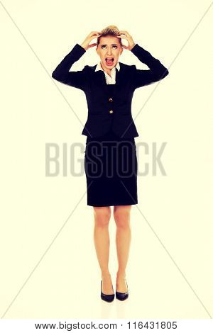 Angry businesswoman pulling her hair and screaming