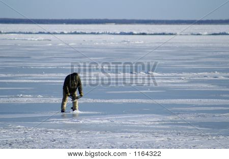 Man Drilling Into Ice With An Auger