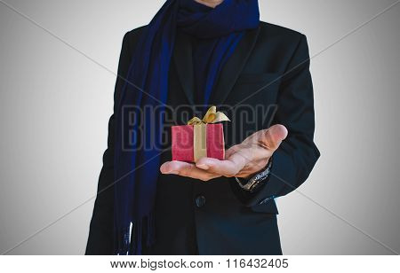 Businessman in casual suit with little gift box on hand, selective focus on gift box