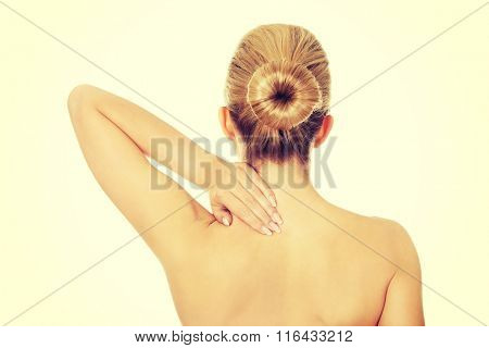 Young topless woman with back pain