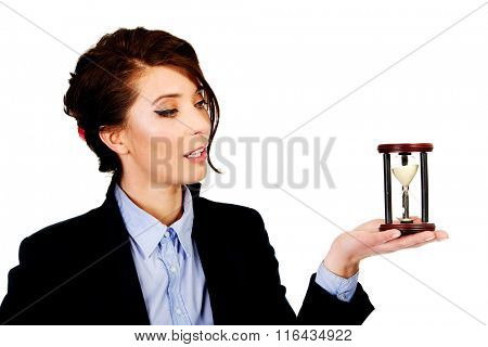 Businesswoman holding hourglass.