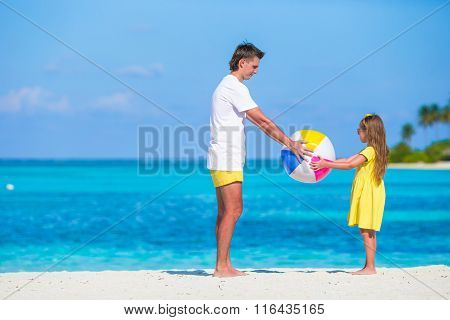 Happy family on the beach with ball having fun together