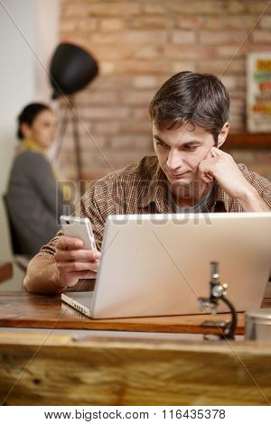 Casual man using mobile and laptop, sitting at desk.