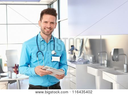 Friendly male physician in doctors room looking at camera, smiling.