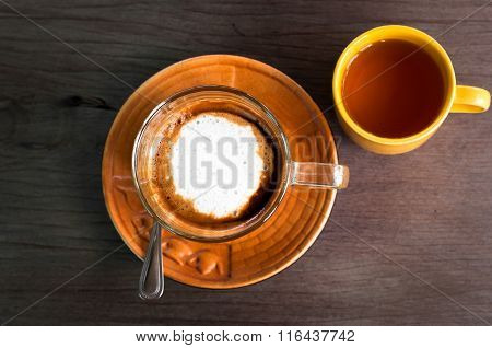 A Cup Of Caramel Cappuccino Coffee In A Transparent Cup On Wooden Background With Hot Tea In Yellow