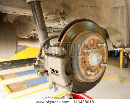 Rear Disc Brake On Car In Process Of New Tire Replacement. The Rim Is Removed Showing The Rear Rotor