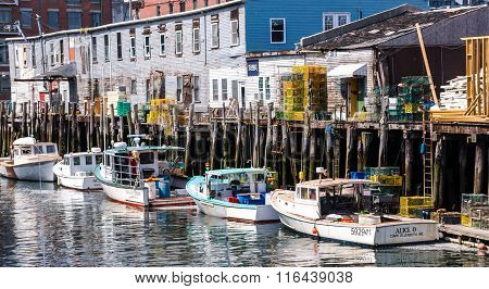 PORTLAND, ME USA  - AUGUST 10 2015: Lobster fishing boats are berthed at dockside in Portland Maine's harbor after delivering the day's catch.
