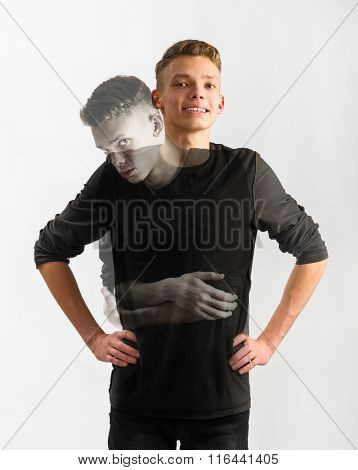 portrait of an insecure male caucasian teenager with two faces on gray background