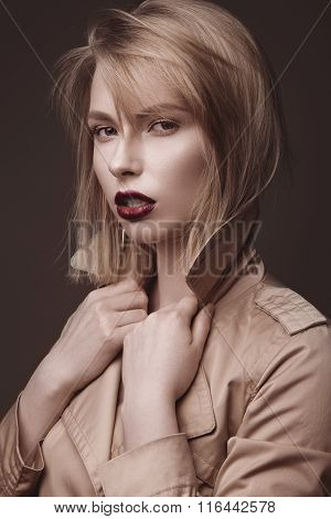 Beautiful blonde woman in a bright coat and dark lips, showing different poses. Beauty face.