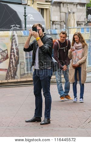 Man With Camera And A Couple Of Young People Behind Him In Haarlem, The Netherlands