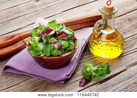 Corn salad leaves, utensils and olive oil on wooden table. Valerianella locusta