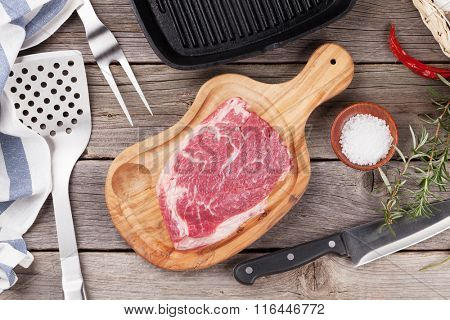 Raw beef steak with spices and herbs and utensils on wooden table. Top view