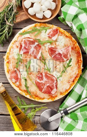 Pizza with prosciutto and mozzarella on wooden table. Top view