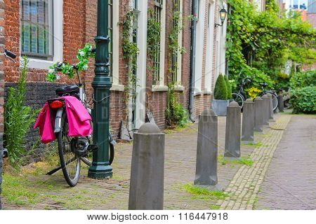 Bicycle With Flower Decorated Handlebars Near A Lamppost On A Narrow Street