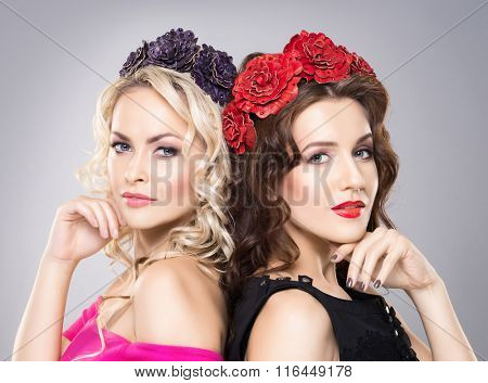 Close-up of two beautiful ladies with pure skin wearing flower alike headbands.