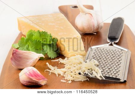 Freshly Grated Parmesan Cheese On A Wooden Board