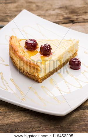Slice Of Cheesecake With Cherry On White Dish