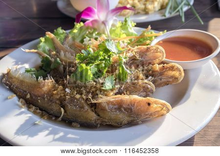Fired Fish With Garlic And Fresh Vegetable On Dish