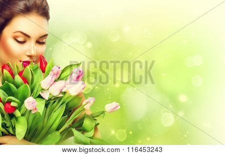 Beauty model Woman with Spring Flower bunch. Beautiful girl with a Bouquet of colorful Tulip flowers