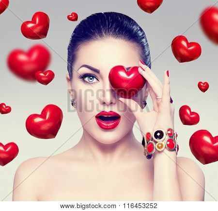 Fashion woman with red hearts. Valentine's day art portrait. Beautiful make up and manicure. Surprised model girl face, open mouth, emotion, love