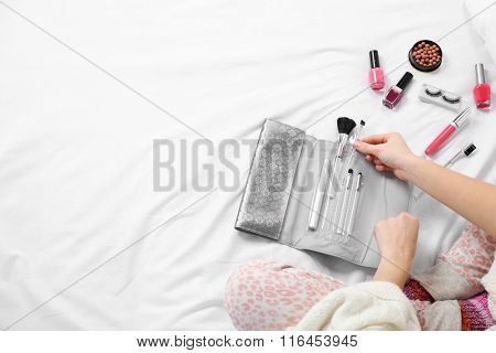 Woman in pajamas applying makeup on her bed