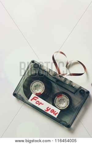 Retro audio cassette with tape in shape of heart on white background