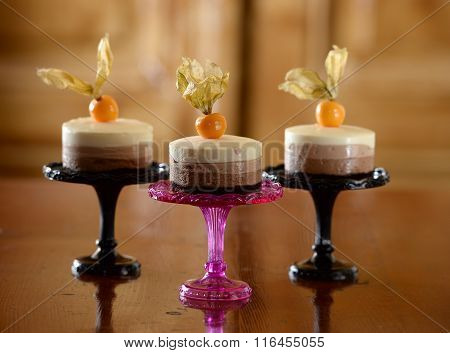 three creamy layered cakes with-physalis on pink and black  stands