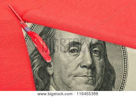 Benjamin Franklin macro peeking through cutting red paper