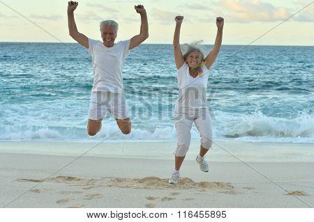 Senior couple  jumping on  seashore