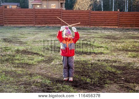 Little Girl Gives Signals With Wooden Sticks