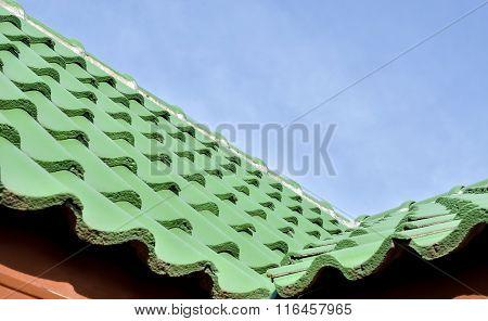 Green roof tile pattern over blue sky