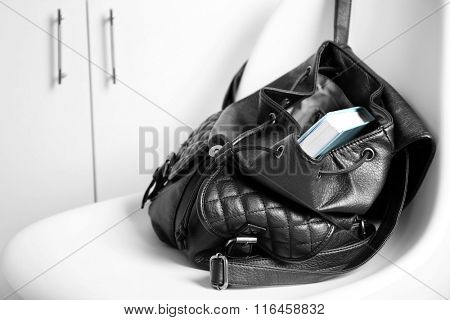 Fashion female backpack with book on white chair, close up