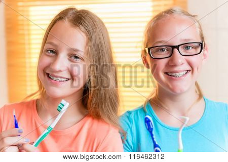 Two girls with dental retainers brushing teeth