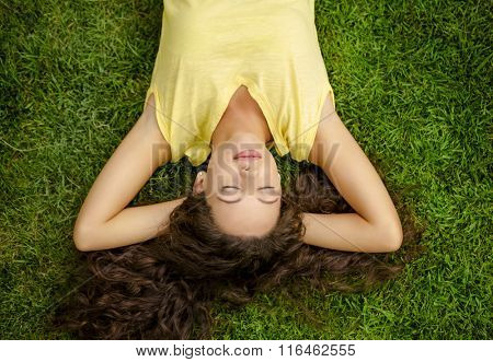 Portrait of a beautiful and happy young woman lying on the grass