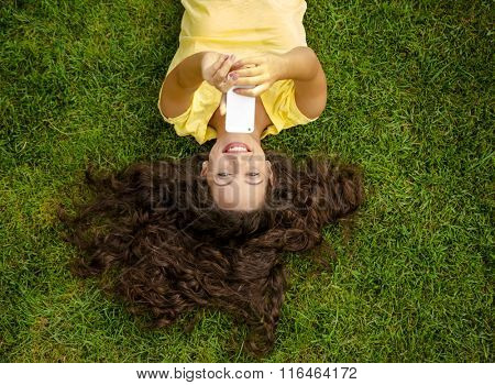 Smiling young woman lying on the grass and making a selfie