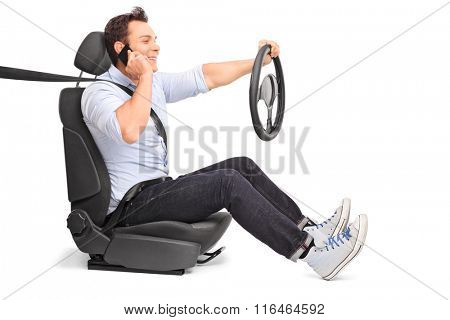 Young man driving and talking on his cell phone isolated on white background