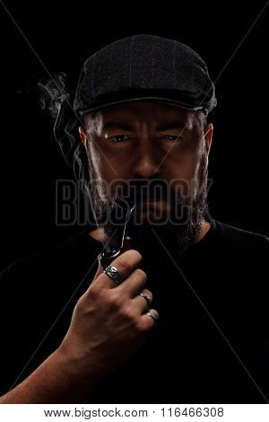 Vertical shot of a man with a beard and a beret smoking a pipe on black background