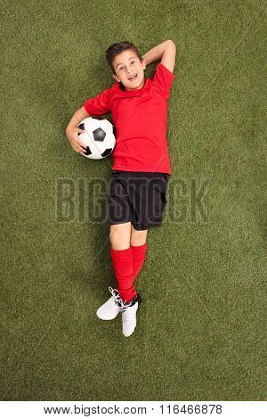 Vertical shot of carefree little boy in a football jersey laying on a grass field and holding a football