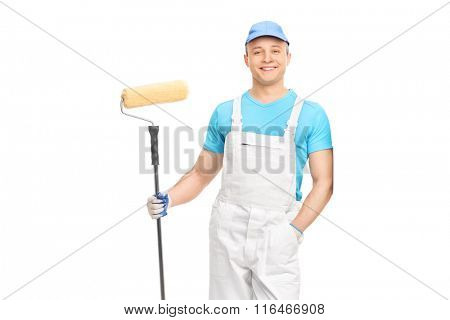 Young male decorator holding a paint roller and leaning against a wall isolated on white background