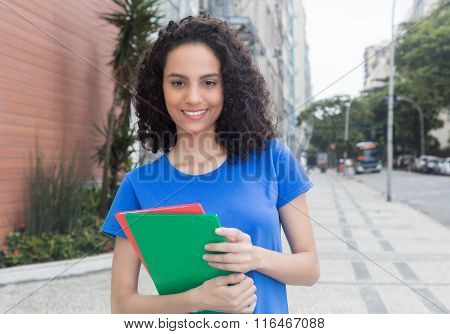 Young Caribbean Student With Books In The City