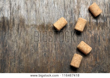 Five wine corks on old wooden background, close up