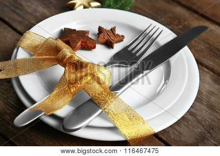 Christmas serving cutlery with plate on a wooden background, close up