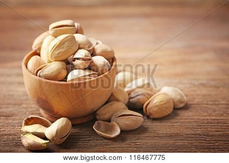 Pistachios in the wooden bowl on the table, close-up