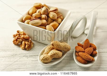 Pistachios, almonds, peanuts and walnut kernels in the ceramic bowl and spoons, on white wooden background