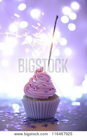 Cupcake with pink cream icing and sparkle on a glitter background, close up
