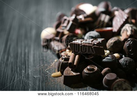 Assortment of tasty chocolate candies and cinnamon on wooden table background