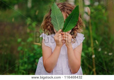 child girl playing with leaves in summer forest with birch trees. Nature exploration with kids. Outd