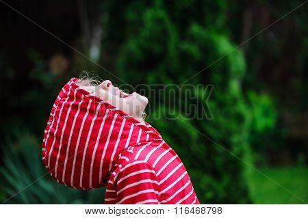 child girl in red raincoat walking in rainy summer garden. Seasonal outdoor activities